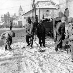 American soldiers checking for concealed mines in a Belgian town during the Battle of the Bulge; December 1944