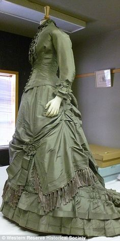 1870's green gown with asymmetrical skirt and fringe.