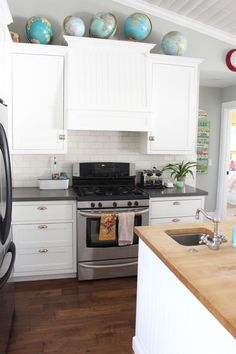 Open, white kitchen cabinets with globe decor
