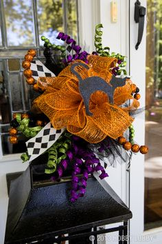 "Create a wreath or ribbon arrangement that's a ""scream"" this year! Use purple, orange, green , and black for a modern spin on Halloween decor."