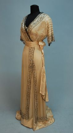 SILK and BEADED NET GOWN, c. 1911. Ivory satin beneath cream net having pleated short sleeve and V-neck decorated with bands of crystal and opalescent white beads in a pattern of daisies, with beaded fringe, the bodice having a band of printed silk and metallic net beneath the cream net layer, satin cummerbund with side drape, net overskirt with off center slit above trained silk skirt.