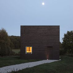 Black-painted timber contrasts with clean white window frames on the walls of this cube-shaped weekend home in Normandy, France hous simpl
