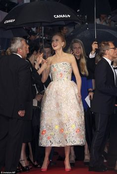 Rainy days: Nicole protects her Dior floral gown with a festival umbrella