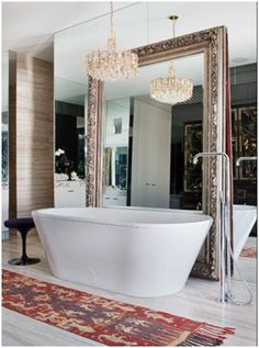 That oversize frame on the mirror in the bathroom is such beautiful idea, mixed with a kilim rug, modern bath, and then add a modern light!! DREAM MASTER BATH