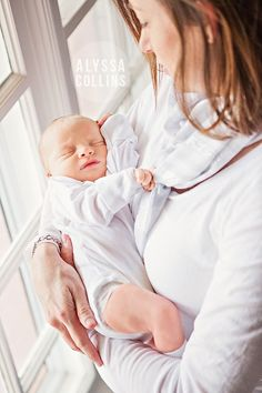Lifestyle newborn session.  Natural light.  Mother holding baby by window.