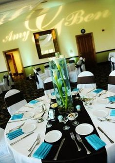 white table cloth, white chair covers, aqua napkins , black table runners and black chair sashes