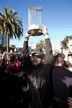 San Francisco Giants relief pitcher Sergio Romo, center, holds up the World Series trophy as he greets fans outside AT Park in San Francisco, Monday, Oct. 29, 2012. The Giants, who defeated the Detroit Tigers in the World Series, returned home to a hero's welcome. (D. Ross Cameron/Staff)
