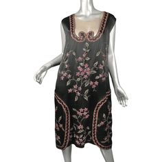 An exceptional quality flapper dress is fashioned from jet black silk charmeuse (satin front/crepe back). The 'trims' are made up of thick metallic gold twist satin stitch, raspberry and pink silk tambour embroidery, amazing silver and gold seed beads, and finished with a chain stitch border. The skirt in the back has an additional panel (the decorative one!) that wraps seamlessly around to the front; it remains open at the front on the sides.