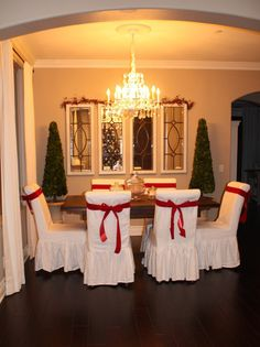Minimal Decor: RMS user happyeastcoasttransplant added red ribbon to each white chair and red-berry garland above the four mirrors. Until guests arrive, glass jars full of holiday candy serve as table toppers. table decorations, setting table, table settings, chair covers, christmas tables, table toppers, tabl set, dining room chairs, holiday tables