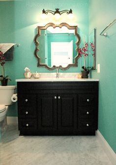 How cute is this bathroom? We love the aqua-colored walls with the neutral tones, and how just the cabinet is painted black with silver fixtures that really pop!