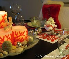 A Christmas Holiday table with red coral and silver ornaments, beach finds and more.