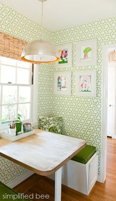 Super cute kitchen nook with green trellis wallpaper and storage in the bench