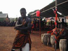 Foto en un funeral africano. Las personas visten de negro o rojo pero tambien en la ceremonia hay danza.