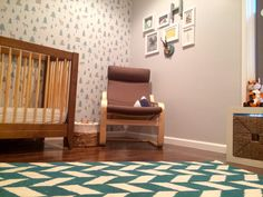 This modern alpine-themed nursery features a wallpaper accent wall and a fab herringbone rug from @Ashley Urban Outfitters!