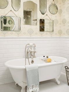 A claw-foot tub basks in the reflection of a wall's worth of vintage beveled mirrors in this bathroom.