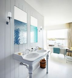 Elle Macpherson's aquatic bathroom with blue tile, double sink, and clawfot tub.