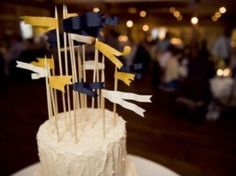 Different flavored round cakes at each reception table with table number stuck into each cake. Guest can choose the cake flavor they desire by visiting other tables. Love the nautical flags too.