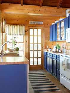 For a low-cost transformation, existing cabinetry was painted blue in this kitchen, giving it a cheery face. New maple countertops and tile flooring in a similar color finished the makeover and brought the kitchen up-to-date.