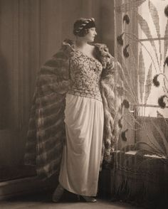 Mrs. Rudolph Valentino models an evening gown and fur cape by designer Paul Poiret.