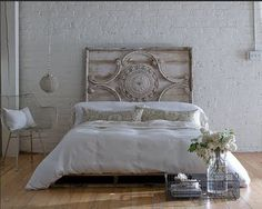 Salvaged metal headboard behind a bed on salvaged pallets. Great recycling!