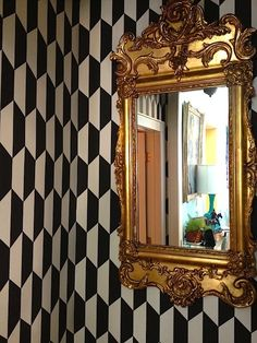 Black and white patterned wallpaper with gold mirror