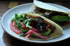 Barbacoa Beef Cheek Tacos with avocado and pickled red onions