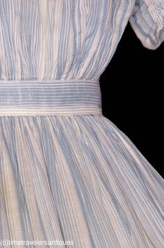 """young miss's one piece powder blue striped muslin Summer dress with a fashionably pleated bodice, ruched sleeves, piped at the neckline, the armscyes, and the waistband, and with a blind back hook and eye closure. The bodice is lined in muslin. The unlined skirt is finely cartridge pleated, with a single slit pocket and a deep faced hem. 15"""" from shoulder to shoulder, a 32"""" bust, 22"""" waist, and 52"""" from shoulder to front hem."""