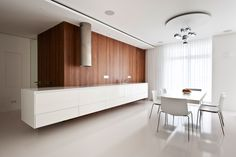 All-white kitchen interior with single wooden accent by Russian architect Alexandra Fedorva.