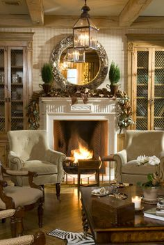 Very pretty, inviting room with greenery on the mantle and a fire roaring.
