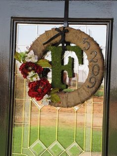 Burlap around a styrofoam wreath, house numbers from Lowes, and dried moss around a letter initial from a craft store!
