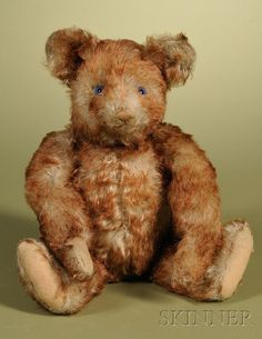 """Rare Steiff Petsy Teddy Bear, Germany, c. 1930, auburn tipped beige mohair, blue glass eyes, stitched nose, mouth, and claws, felt pads, excelsior stuffed with squeaker and original underscored """"f"""" button, ht. 13 in."""