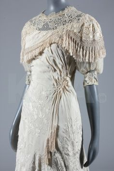 Circa 1910 wedding gown owned by 1960s and 1970s celebrated beauty and model Heidemarie Balzer. She selected garments for herself purely for their aesthetic beauty instead of a couture label. This gown is Cantonese embroidered silk with chiffon puff sleeves and a lavishly embroidered swathed silk over-dress trimmed with fringes and tassels.