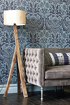 Anthropologie pattern mix in pillow and wallpaper - you could say the tufting in the sofa is sort of a pattern too