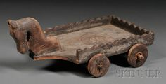 Folk Art Carved Wood Child's Wagon, Continental, 19th century, with horse's head, central flowerhead carving to body, scalloped gallery, and four wheels, ht. 6 7/8, wd. 11, dp. 17 in.