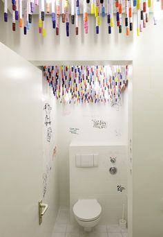 Tulp-designed advertising agency lavatory cubicle has textas attached to the ceiling with magnets inviting users to doodle on the walls