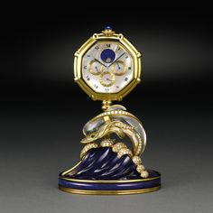GÉRALD GENTA THE DOLPHIN CLOCK A FINE AND RARE YELLOW GOLD, LAPIS LAZULI, ROCK CRYSTAL, MOTHER-OF-PEARL, DIAMOND AND EMERALD-SET PERPETUAL CALENDAR DESK CLOCK WITH PHASES OF THE MOON CIRCA 1990 NO G3160.7 44294