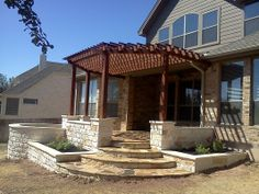 outdoor living space: limestone walls, patio, cedar pergola and flower beds