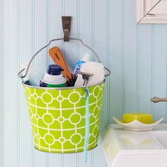 Storage inspiration: A patterned metal bucket hung next to a pedestal sink provides a unique and convenient spot to stow away everyday essentials such as toothpaste, shaving cream, and more.