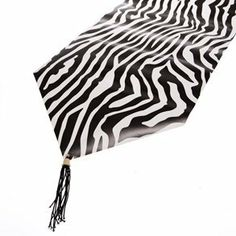 Zebra Print Table Runner by Century Novelty. $3.95. Tableware That Will Bring Out the Animal In You. The Zebra Print Table Runner is the perfect addition to any zoo or animal lover's birthday party! The animal enthusiast in your life will go wild for this Zebra table decoration. Use this safari inspired runner to decorate your table for zoo parties, safari celebrations, and animal print birthday gatherings! Zebra runner is approximately 6 x 11. Black tassels at both ends. Gloss...