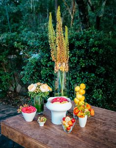 A colorful table arrangement using fruits and flowers.