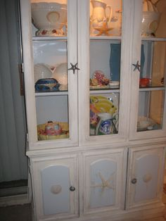 I updated an old china cabinet with ocean blue and antique white paint, sand dollar and starfish