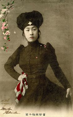 """Japanese Nurse dressed in Black 1905.  Red Cross Nurses were a symbol of modernity and of Japan's commitment to humanitarian ideals, during the Russo-Japanese War (8 February 1904 – 5 September 1905). Postcards reflected this by updating the age old tradition of Bijin-e (pictures of beautiful women). This postcard is from the """"Thousand Contemporary Figures"""" series. S)"""