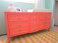 This coral dresser pairs perfectly with an aqua or turquoise nursery! #nurserydesign #coral