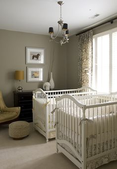 Finnian's Moon Interiors. Gray nursery for 2 with gray walls paint color, white cribs, mustard yellow mid-century modern chair, round ottoman, black chest, gray damask curtain s window panels, yellow crib bedding and gray crib bedding.
