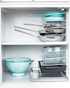 You can remove one pan without having to remove them all. Turn a vertical bakeware organizer on its end and secure it to the cabinet wall with cable clips. Genius! also want those tourquoise pans >:)