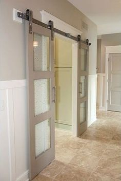 I like this idea, not with a barn door but something more contemporary - Glass-paned sliding barn doors are a modern alternative to traditional French doors and take up a lot less floor space.