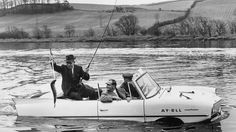 """16th January, 1964: """"On the day after the official opening of the Tay Salmon Rod Fishing Season, Duncan McGregor catches an 8lb salmon from Ian Cameron's amphibious car 'Ay-Ell'."""""""