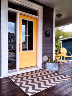 Front porch with stained cedar. Yellow door and chevron rug make it pop.  <3