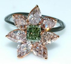Green Diamond in center surrounded by several large colorless Diamonds in a ring setting.