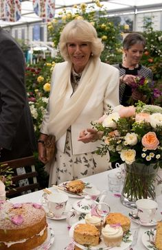 Camilla of Wales 5/20/2013100th  Chelsea Flower Show.  Is Duchess of Cornwall a foodie?  She is always being photographed biting into a morsel or standing close to a food display!